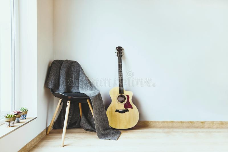 Contemporary home interior. Black chair covered with woolen gray blanket and acoustic guitar in front of an empty white wall. stock photo