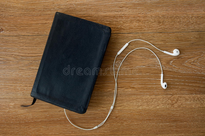 Contemporary image of a Bible with headphones. Hearing the voice of God concept royalty free stock image