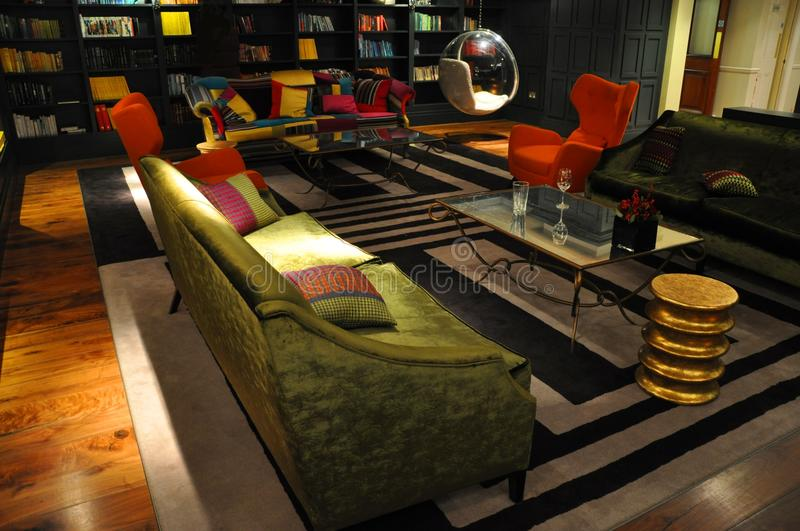 Contemporary interior red armchair,green sofa. Plush stylish interior of an urban luxury lounge Contemporary room with opulent green sofa bright colors and a royalty free stock images