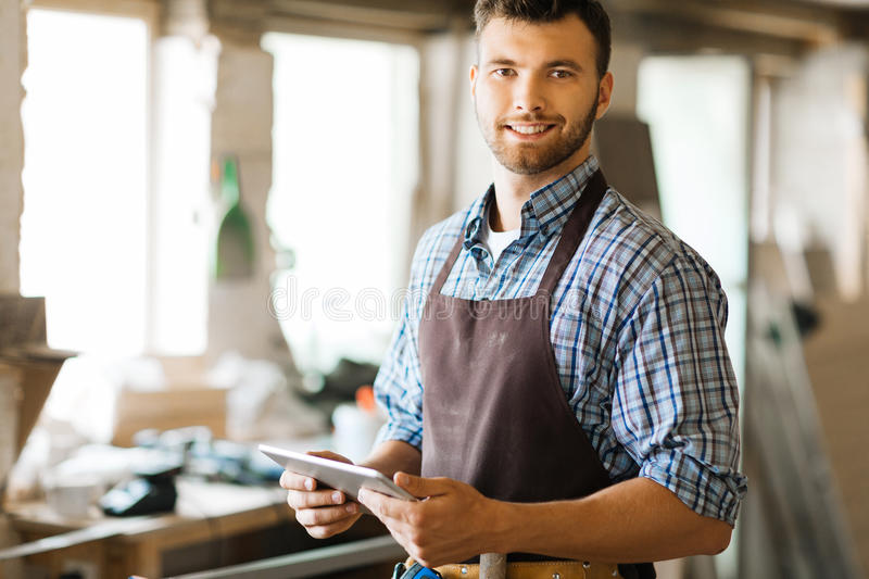 Contemporary joiner. Happy joiner with touchpad networking in his own workshop stock photography