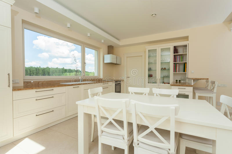 Contemporary kitchen with big white table stock photography