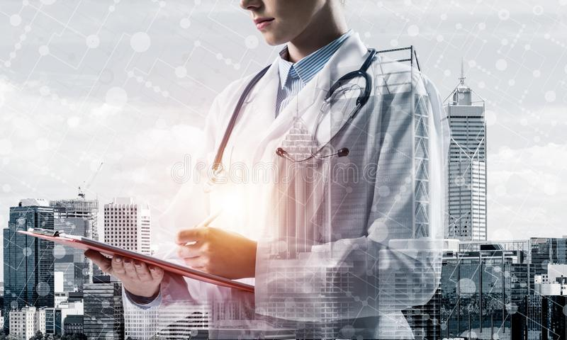 Contemporary medical industry presented by means of female docto. Side view of confident female doctor in white sterile coat making notes in notebook while royalty free illustration