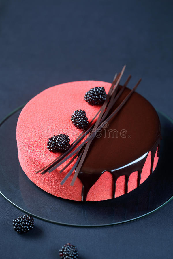 Contemporary Multi Layered Mousse Cake. Covered with Red Velvet Cocoa Spray and Chocolate Glaze, decorated with Blackberries and Chocolate Elements, on a dark royalty free stock image