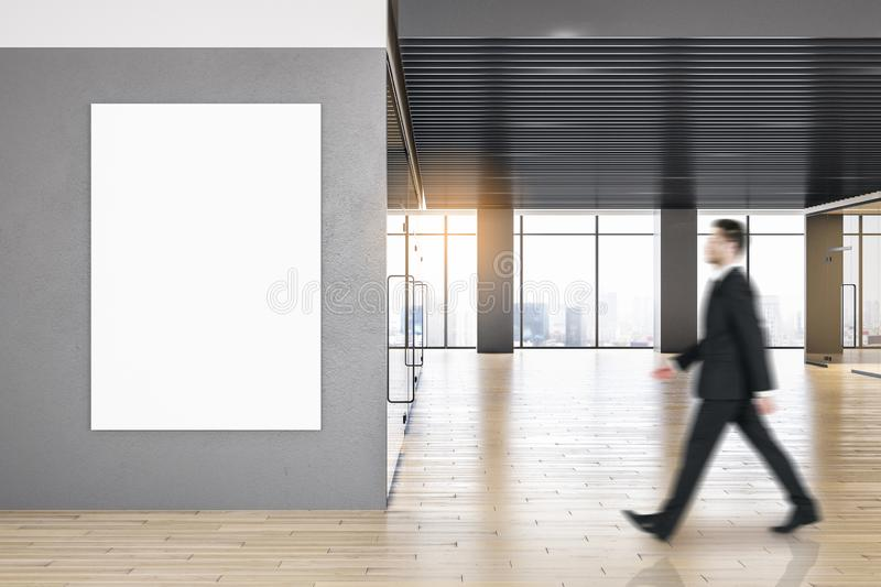 Contemporary office interior with poster. Side view of businessman walking in contemporary office interior with empty poster, city view and daylight. Mock up stock photo