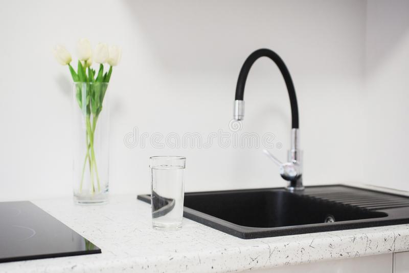 Contemporary sink in the luxury new kitchen. Modern apartment. Contemporary faucet. New black sink. Modern kitchen in house. A stock image