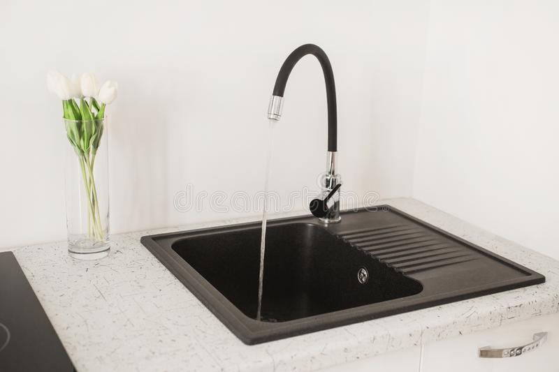 Contemporary sink with tap in the luxury kitchen. White luxury furniture. New black open faucet. Modern apartment. Water flow from stock photo