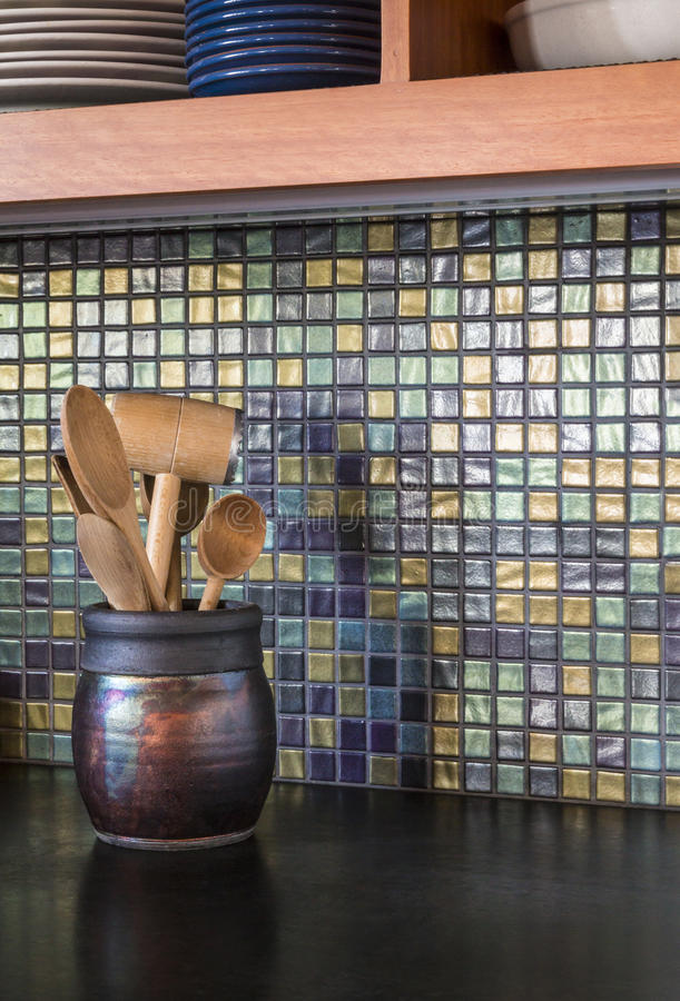 Contemporary upscale home kitchen detail of glass tile mosaic backsplash and concrete countertop. Detail of contemporary upscale home kitchen interior with stock photos