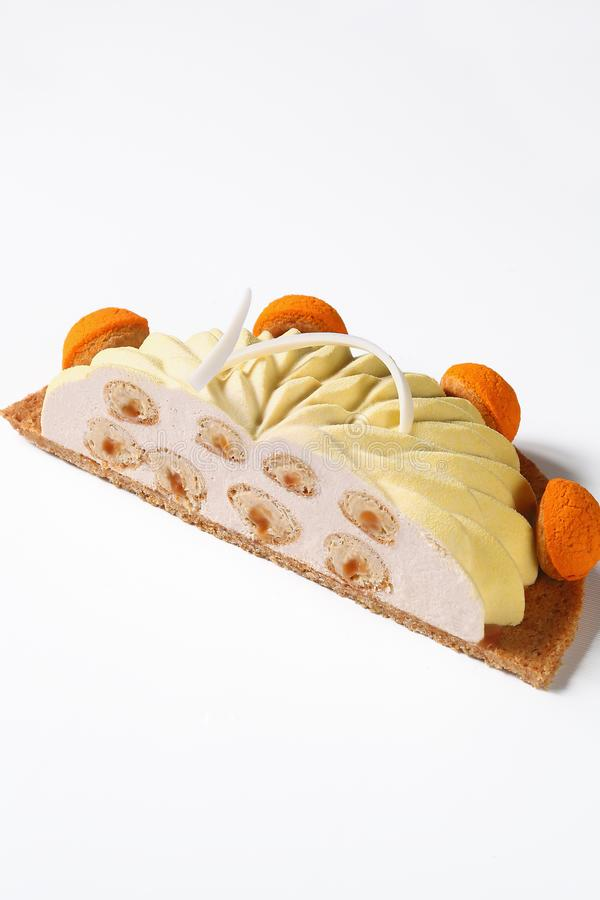 Contemporary version of the famous french Saint Honore Cake. Decorated with choux buns with craquelin - crispy cream puffs, covered with yellow velvet spray stock image