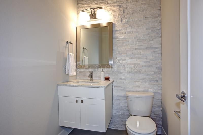 Contemporary white and gray bathroom. Features stone accent wall framing a white bathroom vanity under a silver beveled mirror illuminated by double sconces royalty free stock photo