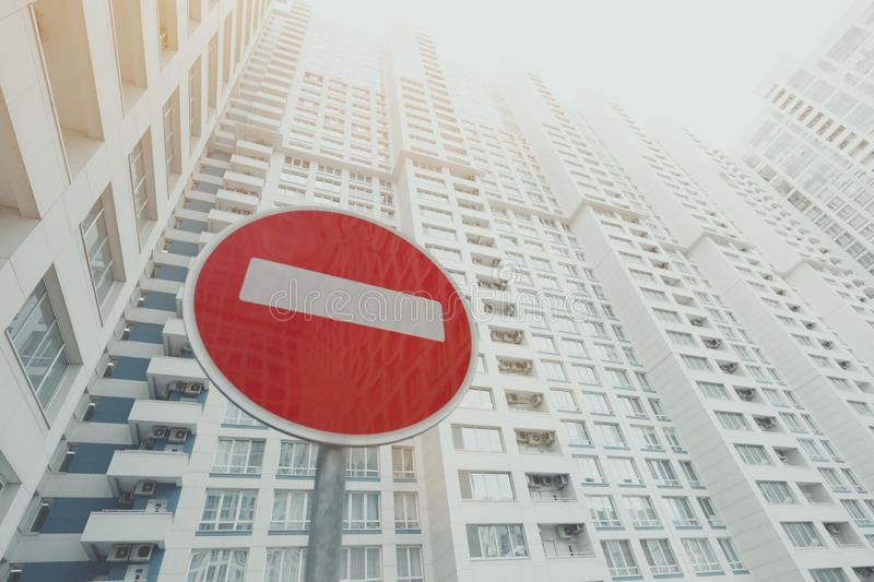 Contemporary white and grey skyscraper, red stop road sign below. Contemporary white and grey skyscraper apartment building with a lot of regular balconies and stock images