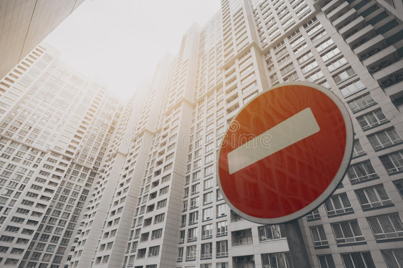 Contemporary white skyscraper building with a red stop road sign. Contemporary white and grey skyscraper apartment building in Moscow on a sunny day with a red stock photography