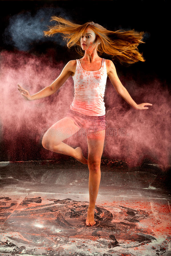 Contemporary dance girl spin pink blue powder. Expressive dance movement of a woman contemporary ballet dancer on stage with a black background with blue and royalty free stock images