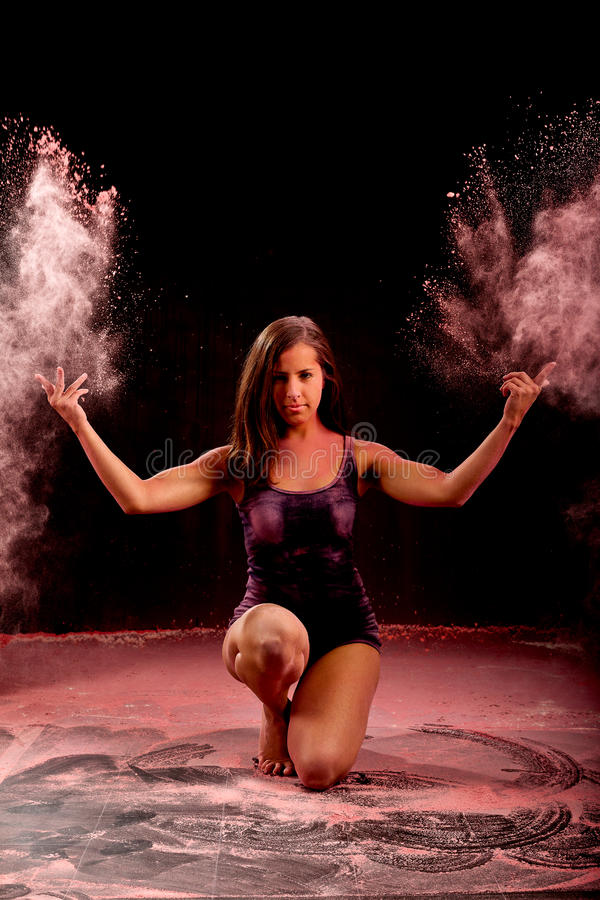 Contemporary dance girl throwing pink powder. Expressive dance movement of a woman contemporary ballet dancer on stage with a black background who throws pink stock photography