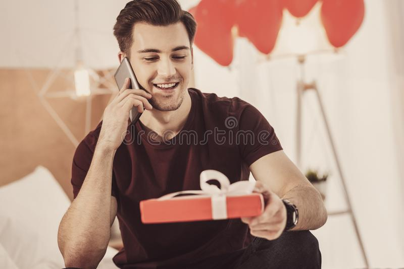 Contended young man preparing present for his wife while sitting in living room stock photos