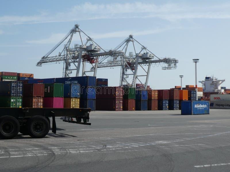 Contenedores coloridos apilados y dos grúas en un terminal en el puerto marítimo de Le Havre, Francia fotografía de archivo libre de regalías