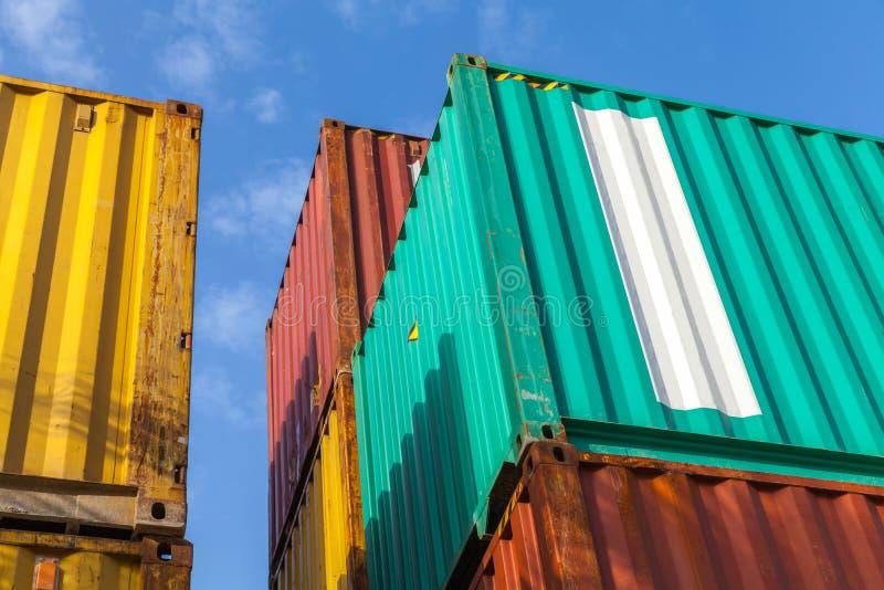Contenedores para mercancías del metal colorido debajo del cielo nublado azul fotos de archivo