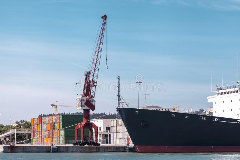 Contenedores para mercancías en el puerto La grúa marina levanta el contenedor para mercancías Transporte de las importaciones/ex fotos de archivo