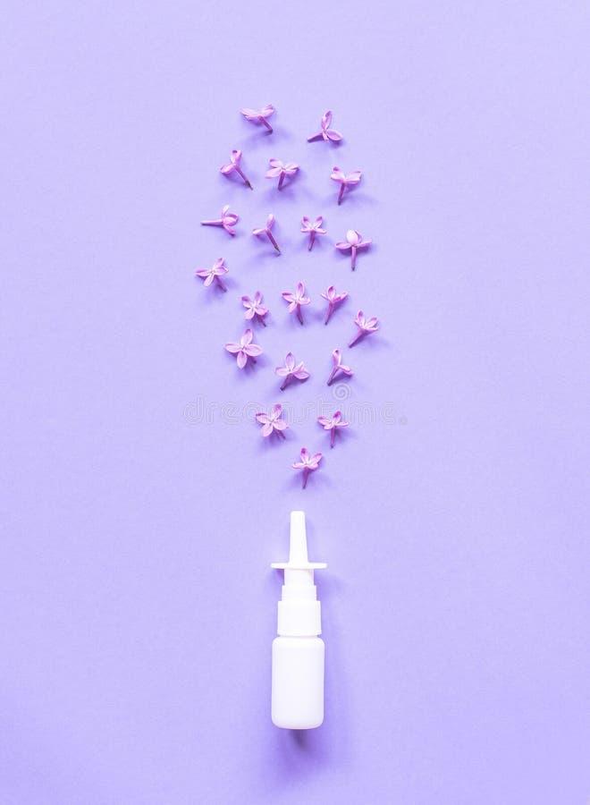 Conteneur blanc de pulvérisation nasale sur le fond violet, solution de l'eau saline pour le traitement de congestion de nez et a images libres de droits