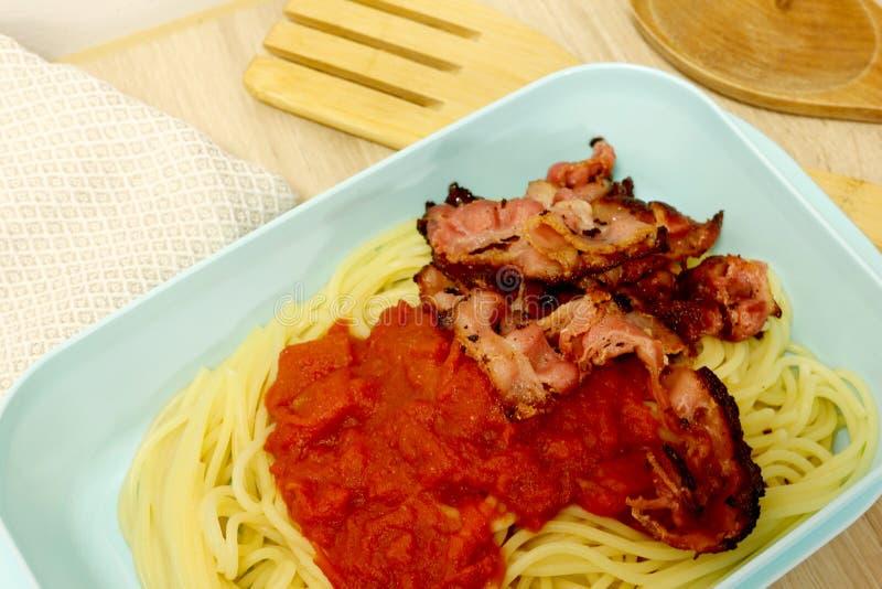Conteneur de nourriture en plastique rempli de sauce de lard et tomate et de spaghetti photos stock