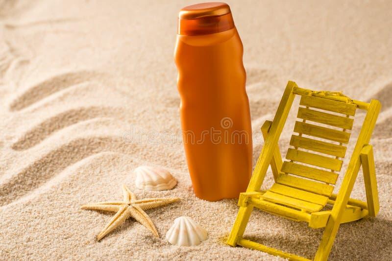 Conteneur et seashells de lotion de bronzage sur le sable photo libre de droits