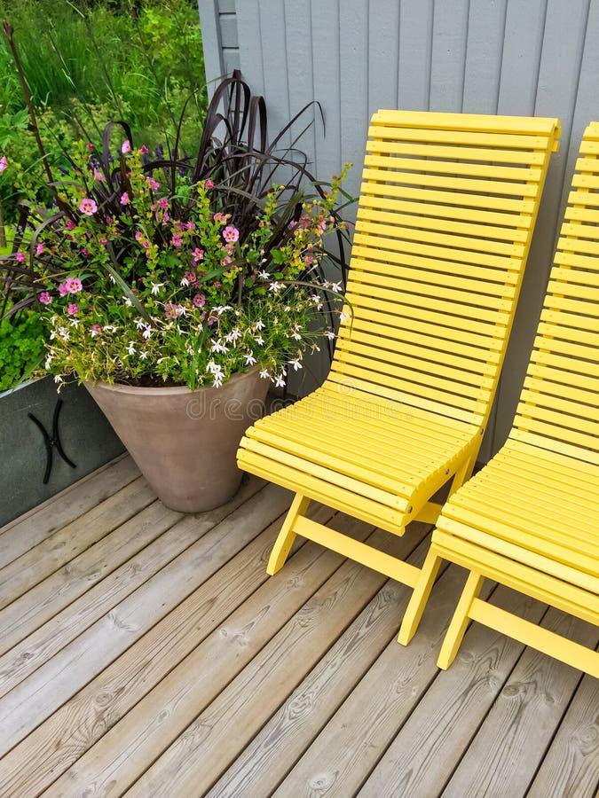 Contenga el exterior adornado con las sillas y las flores amarillas fotos de archivo libres de regalías