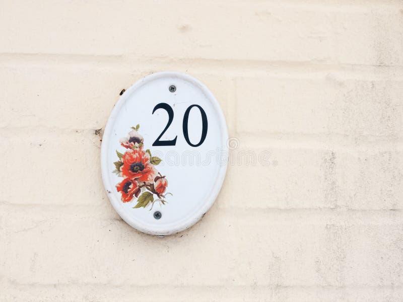 contenga el número de matrícula en el diseño floral blanco del número 20 de la pared del exterior fotografía de archivo