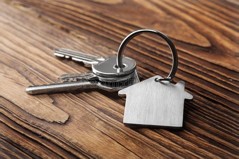 Contenga la llave en llavero formado casa en entarimados de madera imagen de archivo