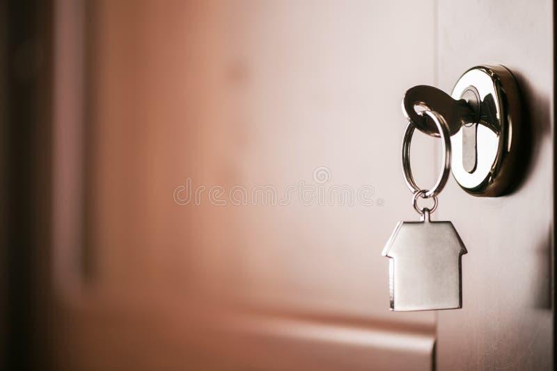 Contenga la llave en un llavero de plata formado casa en la cerradura de un entr imagenes de archivo