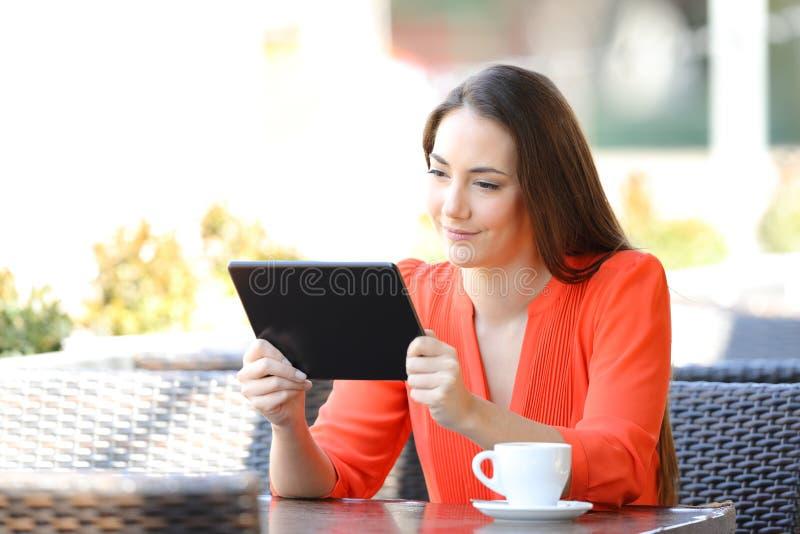 Contenido en línea de observación de la tableta de la mujer seria en una barra fotos de archivo libres de regalías