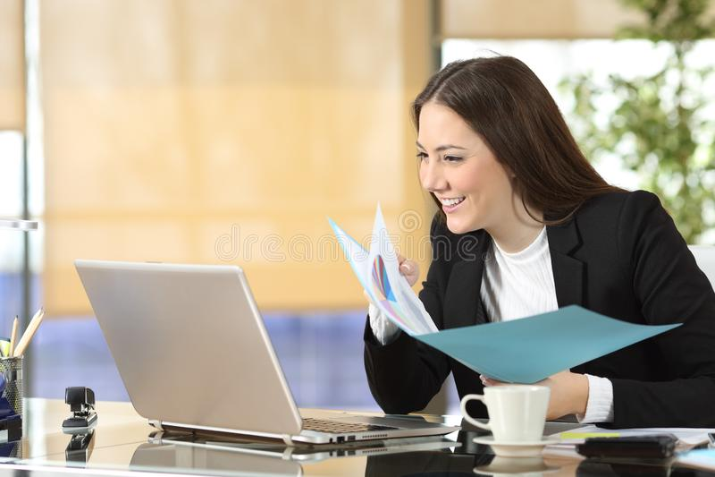 Contenido y documentos ejecutivos felices del ordenador portátil que comparan fotografía de archivo libre de regalías
