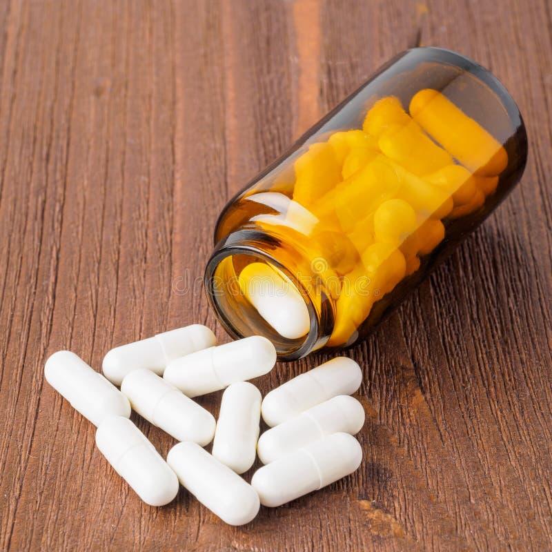 Contenitore aperto con un medicinale, barattolo di vetro con le pillole su marrone fotografia stock libera da diritti