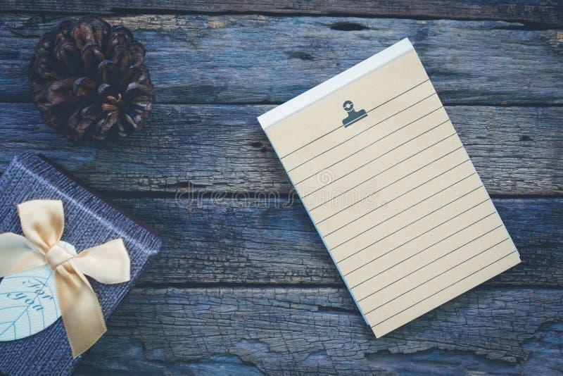 Contenitore attuale di carta per appunti della pagina in bianco, e seme di pino su legno rustico immagini stock libere da diritti