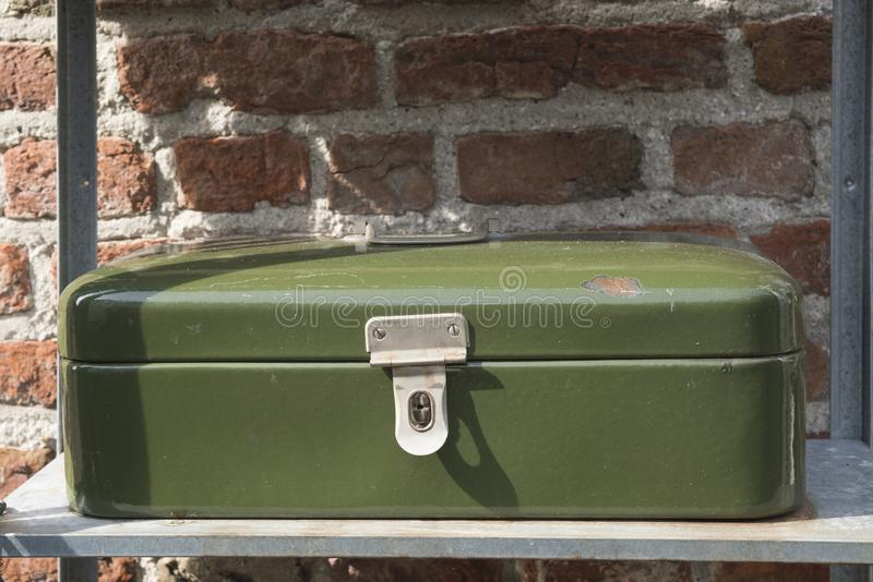 Contenitore d'annata verde di metallo per pane o soldi, sullo scaffale del ferro, contro il muro di mattoni immagine stock