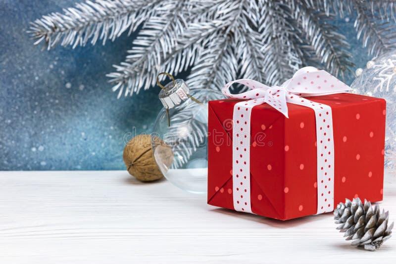 Contenitore, dado e pigna di regalo sulla tavola bianca di legno contro la b blu fotografie stock libere da diritti
