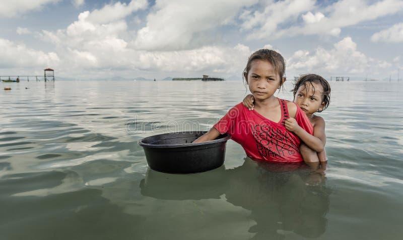 Contenitore della tenuta della bambina della tribù di Bajau e barca turistica avvicinata a per chiedere all'alimento di mangiare, fotografia stock