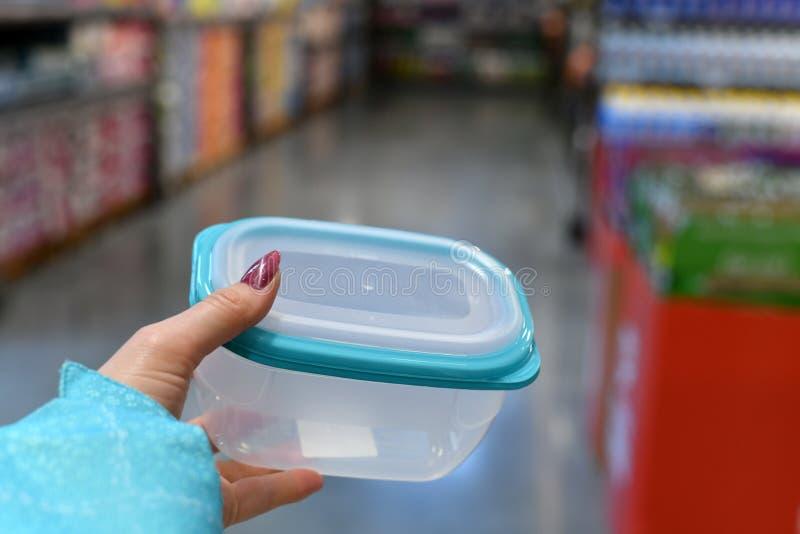 Contenitore di alimento di plastica in mano femminile sul fondo del negozio fotografia stock libera da diritti