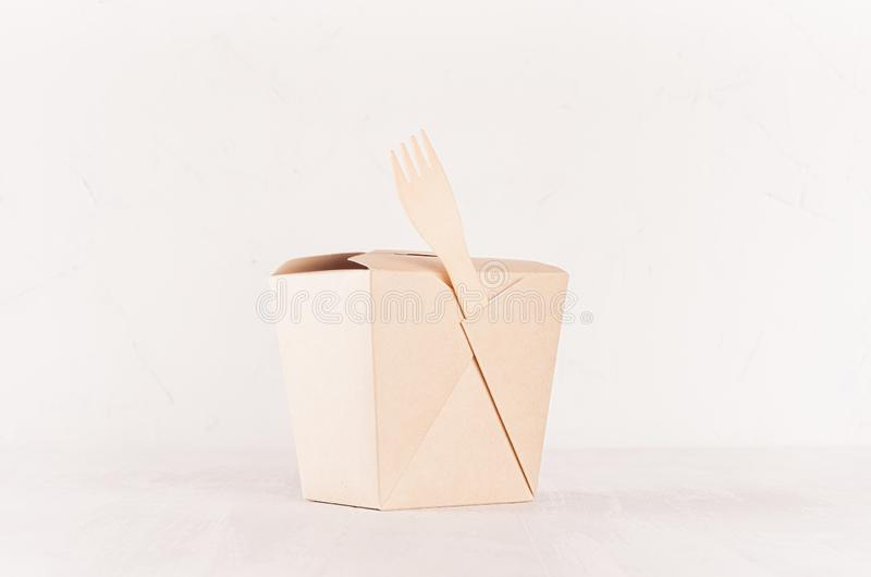 Contenitore di carta marrone di tagliatelle dello spazio in bianco e forcella di legno per alimento asportabile sul fondo bianco  fotografia stock
