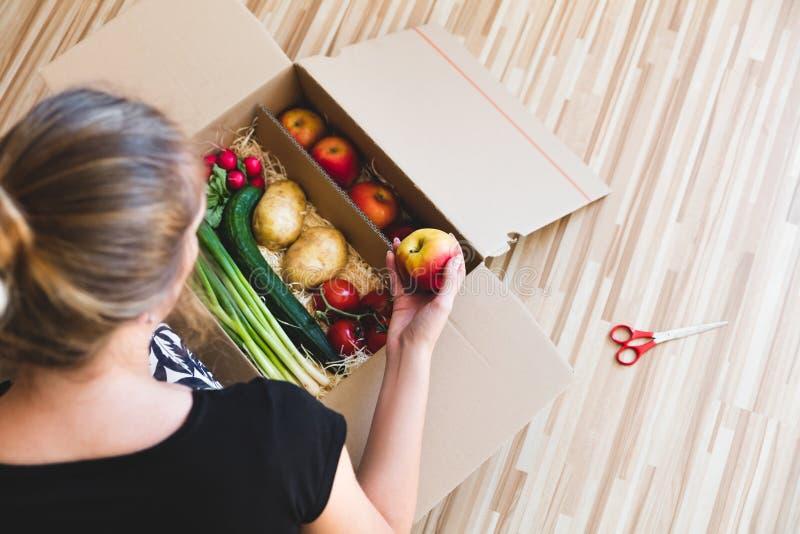 Contenitore di drogheria delle verdure, donna che tiene una mela fotografie stock libere da diritti