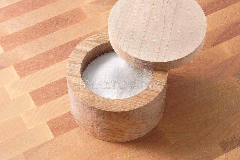 Contenitore di legno di sale sulla scheda di taglio di legno immagine stock libera da diritti