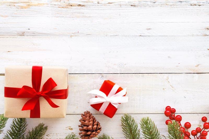 Contenitore di regali del regalo di Natale ed elementi rossi di decorazione su fondo di legno bianco immagine stock