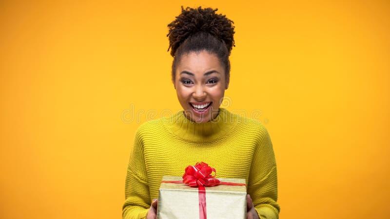 Contenitore di regalo afroamericano emozionante della tenuta della donna, sorpresa piacevole di compleanno immagini stock