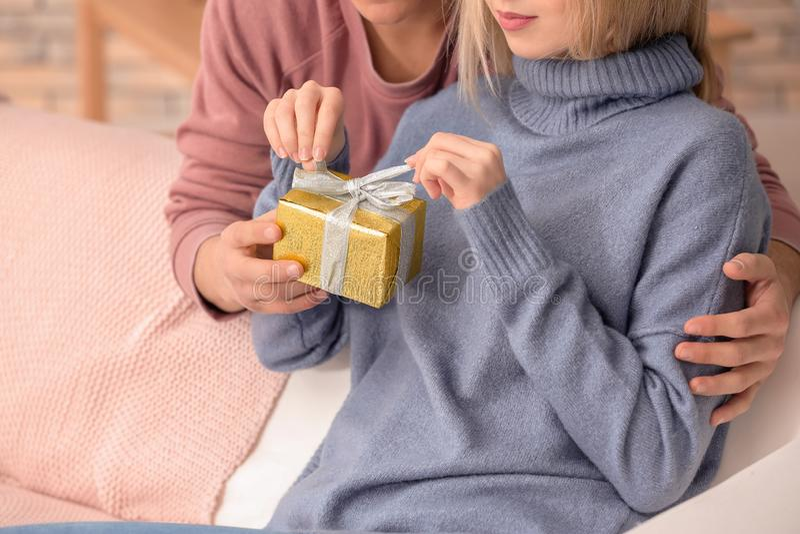 Contenitore di regalo di apertura della giovane donna dal suo ragazzo a casa, primo piano immagine stock