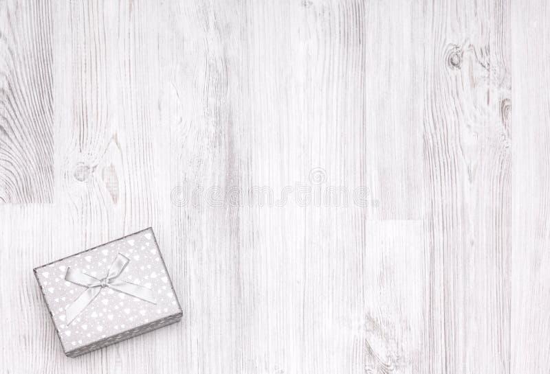 Contenitore di regalo bianco di Natale sul bordo di legno immagini stock libere da diritti