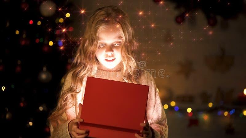 Contenitore di regalo biondo adorabile di apertura della ragazza, atmosfera magica di Natale, effetto d'ardore fotografia stock