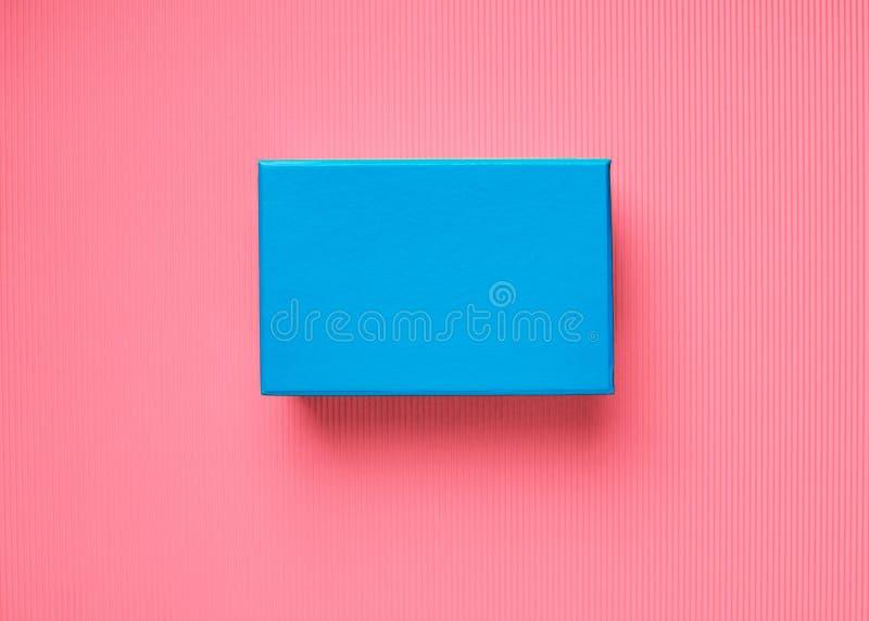 Contenitore di regalo blu su fondo di corallo rosa fotografia stock