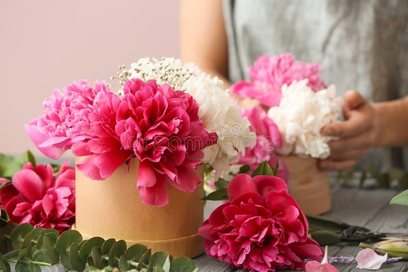 Contenitore di regalo con i bei fiori ed il fiorista femminile che lavorano alla tavola fotografia stock