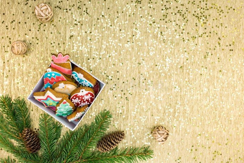 Contenitore di regalo con i biscotti del pan di zenzero su fondo dorato fotografia stock