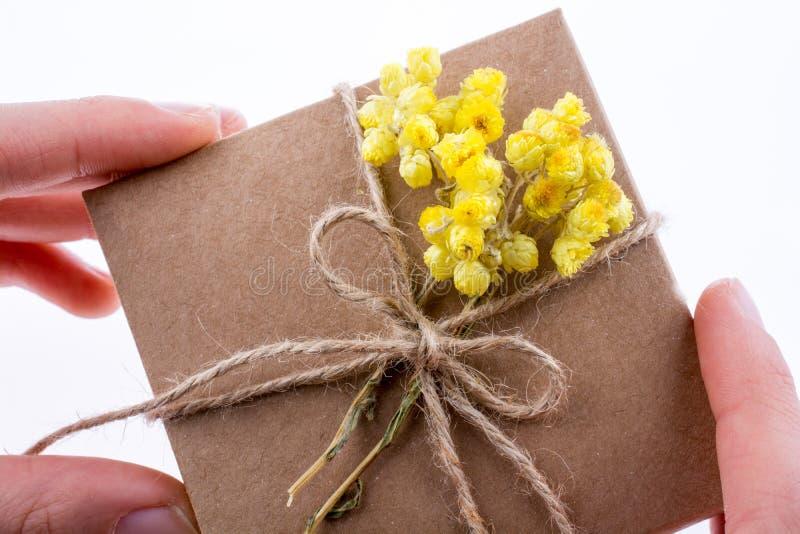 Contenitore di regalo con i fiori a disposizione fotografia stock libera da diritti