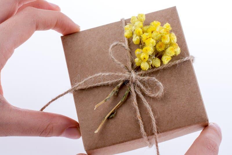 Contenitore di regalo con i fiori a disposizione immagini stock libere da diritti