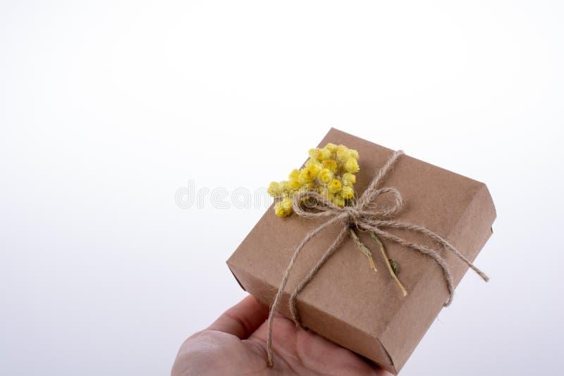 Contenitore di regalo con i fiori a disposizione immagine stock